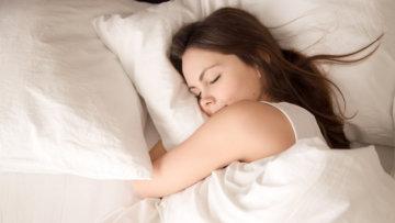 寝て空腹を抑える女性