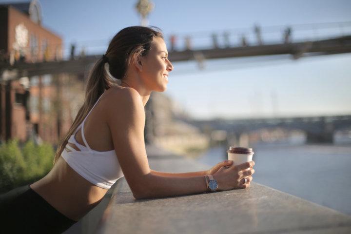 川沿いで笑顔でコーヒー飲む女性